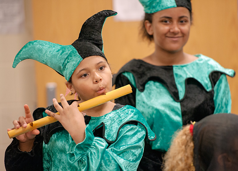 Kid dressed as a jester plays the flute.