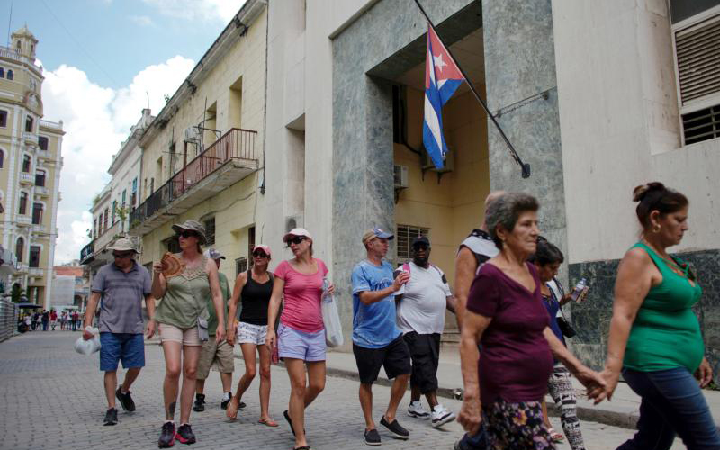 A group of U.S. tourists from a cruise ship walk through a street in Havana June 5, 2019. Days after the Trump administration announced it was placing new restrictions on U.S. travel to Cuba, Archbishop Timothy P. Broglio of the Archdiocese of the Military Services in Washington, criticized the policy, saying the transformation of the island, and the survival of the church there, depends on outside contact. (CNS photo/Alexandre Meneghini, Reuters) See CUBA-RESTRICTIONS June 6, 2019.