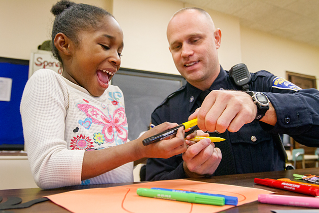 First-grader Jayla Simms laughs while Rochester police officer Jim Perry jokes about putting mismatching caps on her markers Oct. 31 at School 36, Henry W. Longfellow School. Perry, who patrols on the west side of Rochester, spends time with first graders once a week as part of Generation Two mentoring. This is Perry's second year volunteering with the program.