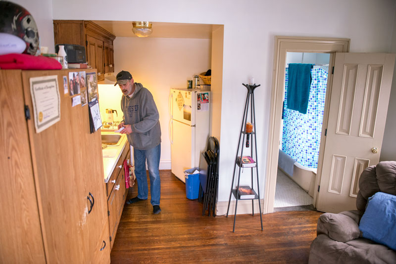 Jim Swan tidys his kitchen while at his home in the Dorothy Day House, a Housing First project that places homeless people.