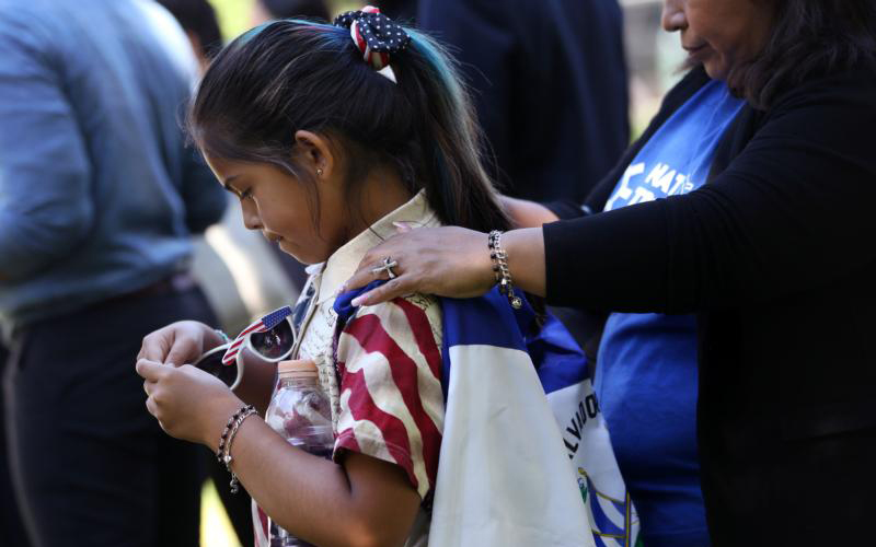 "As members of different advocacy groups organize for a rally outside of the U.S. Capitol in Washington June 4, 2019, Marilyn Miranda, 9, has a Salvadoran flag affixed to her back by her mother, Soledad Miranda, who has Temporary Protected Status. Bishop Joe S. Vasquez of Austin, Texas, chairman of the U.S. bishops' Committee on Migration, applauded the House of Representatives for passing the American Dream and Promise Act of 2019 June 4, which would provide a pathway to citizenship for qualifying ""Dreamers"" as well as TPS and Deferred Enforced Departure holders. (CNS photo/Leah Millis, Reuters) See VASQUEZ-DREAMERS-TPS June 5, 2019."