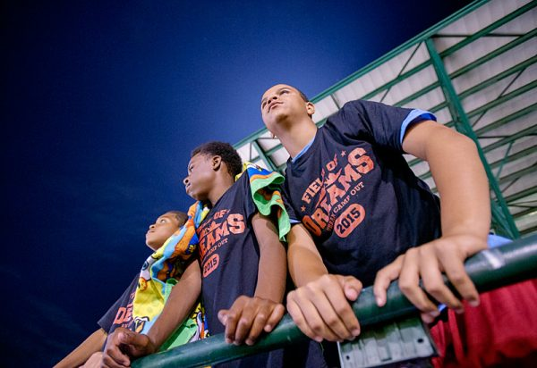 Kids watch baseball game.