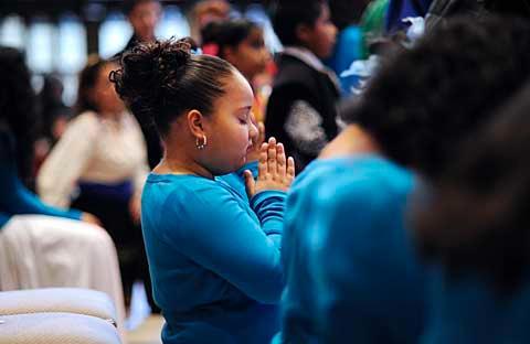 Girl kneels in prayer.