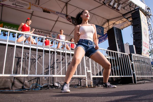 A girls dances in front of a stage.