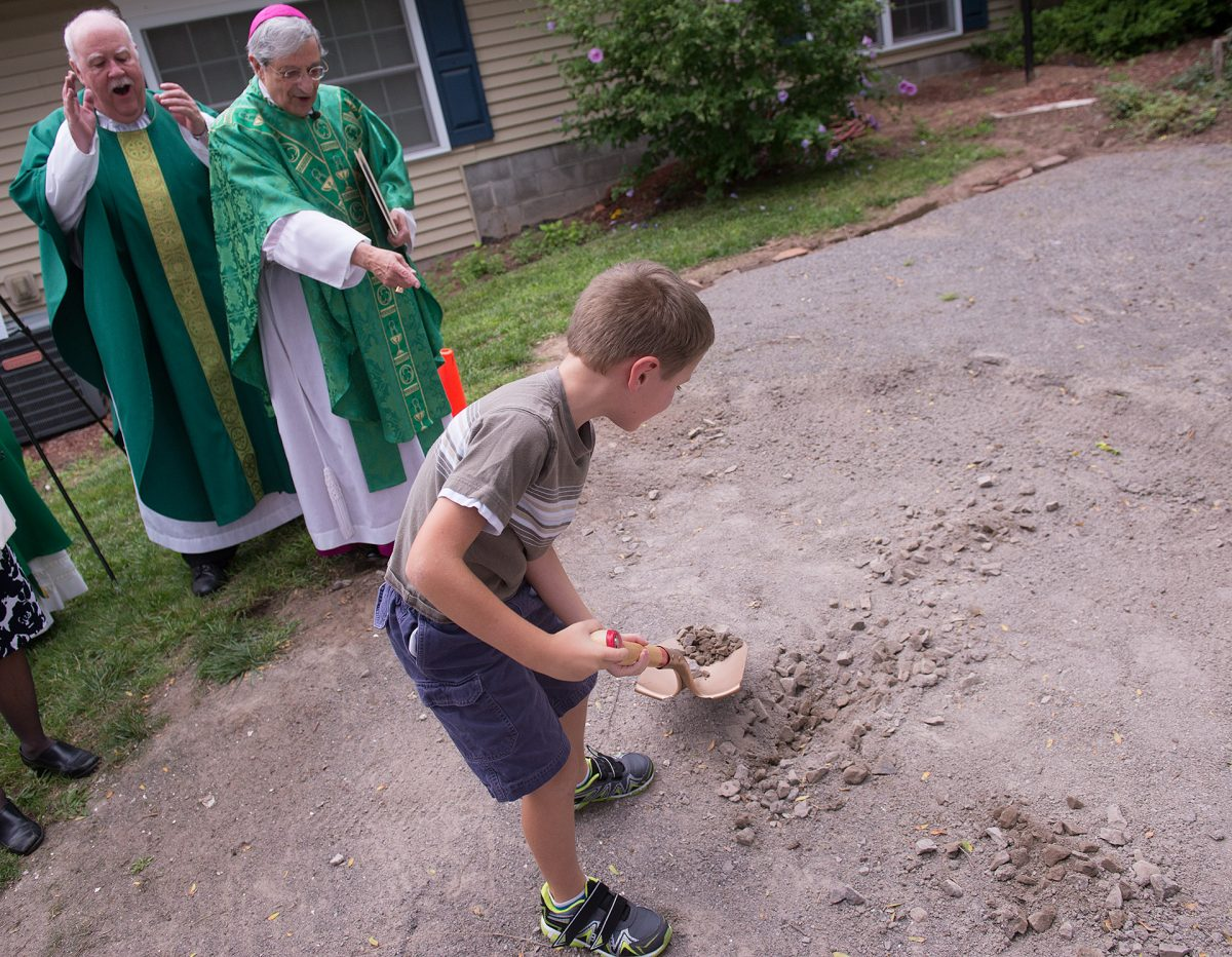 Edward Schofield ,8, of Brockport turns-over  a shovelful of soil as Bishop Salvatore Matano and Father Joe McCaffrey look on during a groundbreaking ceremony for Nativity of the Blessed Virgin Mary Church new Parish Center on Aug. 25 in Brockport. (Courier Photo by John Haeger)