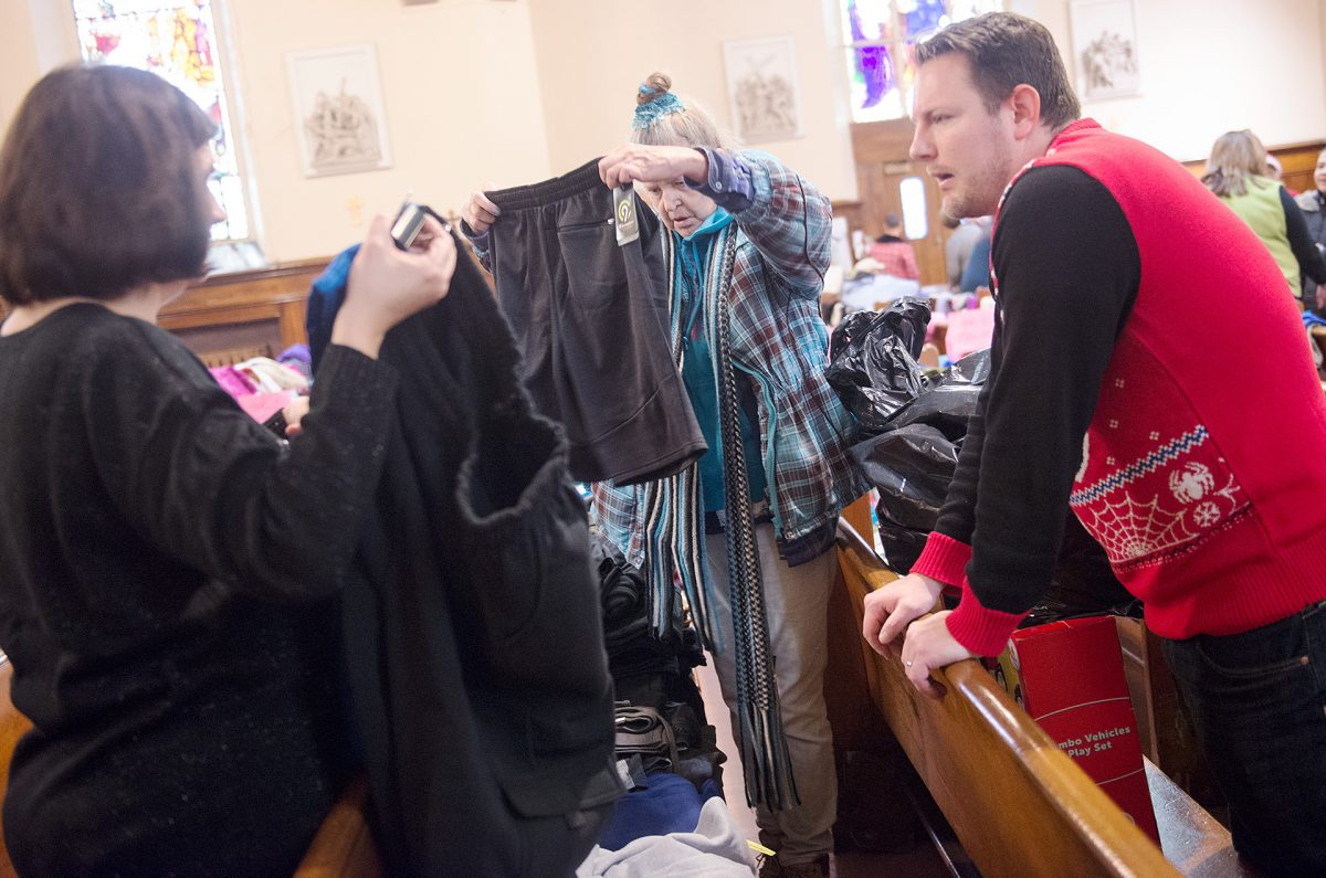 Gina Crawford ,left and Greg Fassler help Linda Malowsky pick out coats during the Christmas giveaway at Holy Apostles Church in Rochester on Dec. 19. More than 100 families were helped by the event which also included a food basket. Courier Photo by John Haeger.