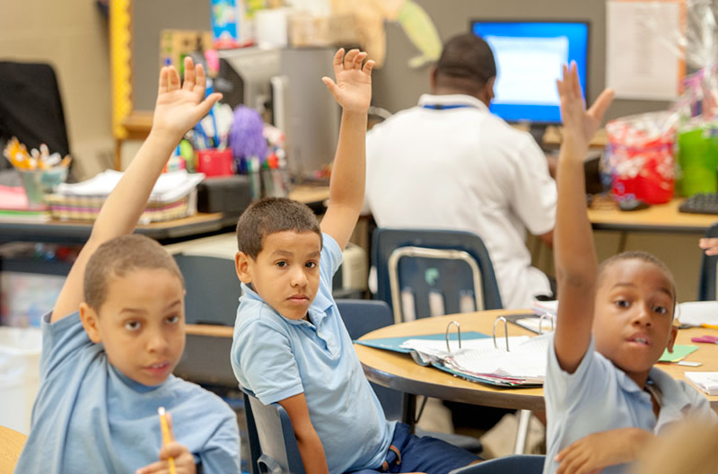 Third-graders Angel Sepulveda-Lopez (from left), Freitty Garcia and Esaiyu Joseph raise their hands during math class June 24, 2015 at Eugenio Maria de Hostos Charter School in Rochester.