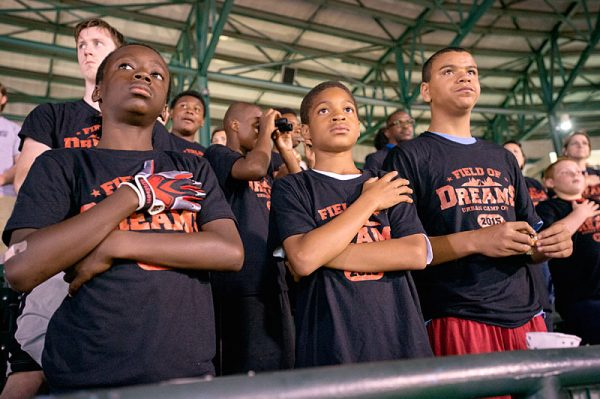 Kids stand for national anthem.