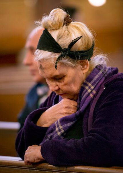 A woman kneels in church.