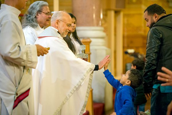 A priest gives a boy a high five.