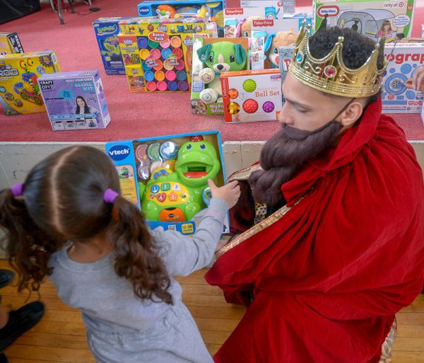 A man dressed as a king hands out a gift to a child.