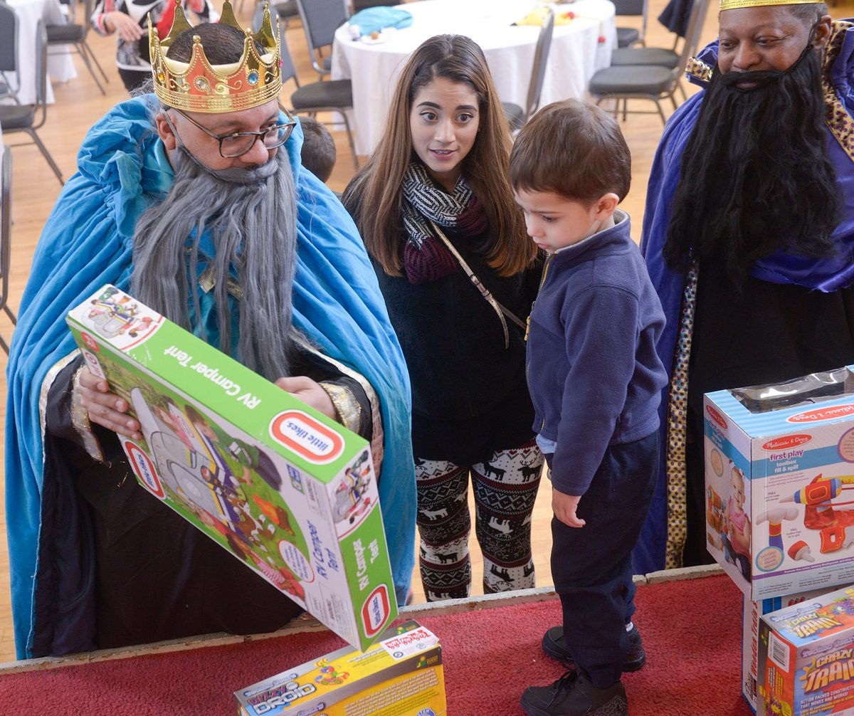 Ray Mayoliz who portrays one of the Three Kings presents Jovani Ortiz with a gift as Cristal Santiago looks on during the Latinas Unidas Three Kings event held at St. Michael's Church in Rochester on January 26. EMC photo by John Haeger)