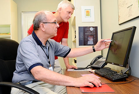David Kyle (top) meets with Bob Wolf, an access team volunteer, who researches a web site with him at St Joseph's Neighborhood Center in July.