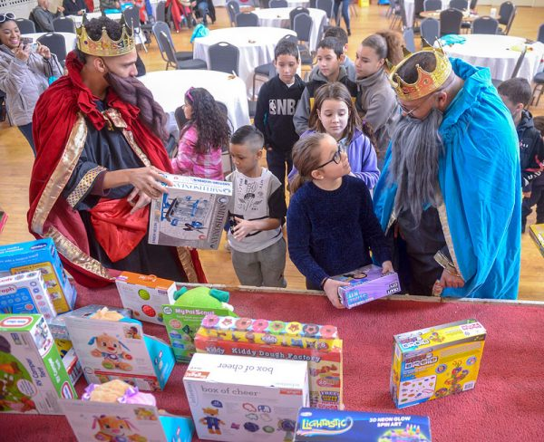 Men dressed as kings present gifts to children.
