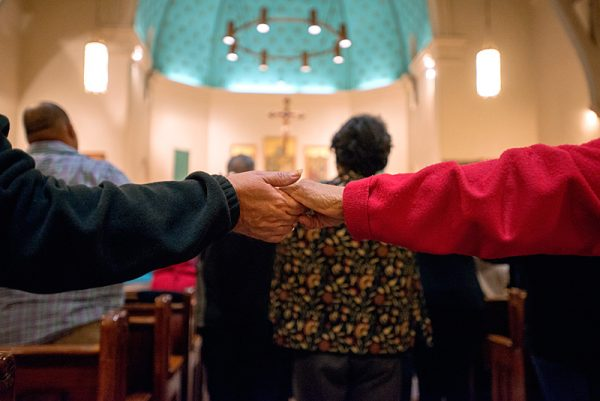 People hold hands in church.