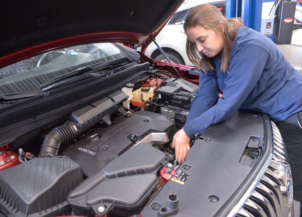 Niki Davey works to remove an O2 sensor from a vehicle for testing during a class at the MCC Auto Tech Program on Oct. 18, in Rochester.(EMC Photo by John Haeger)