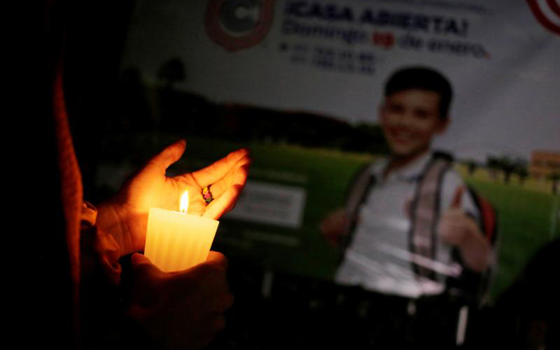 A woman in Torreon, Mexico, holds a candle outside the Colegio Cervantes school Jan. 10, 2020, after a shooting that same day. An 11-year-old student killed a teacher and wounded six other people. The shooter is believed to have killed himself, according to police. (CNS photo/Daniel Becerril, Reuters) See MEXICO-SCHOOL-SHOOTING Jan. 13, 2020.