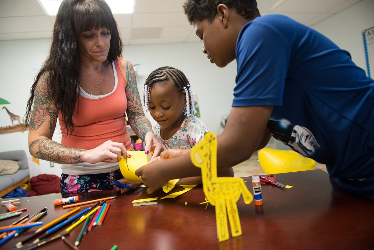 Amanda McGuire and Markus Reed help Laiyahni McKnight cut out a giraffe  during the Summer Learning program held at MMC in Rochester on July 26. (EMC Photo by John Haeger)