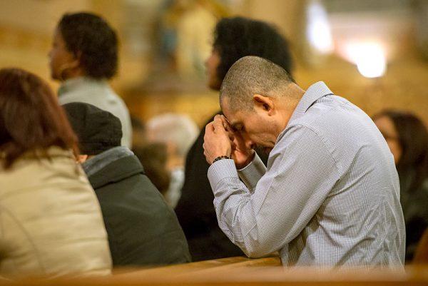 A man kneels in prayer.