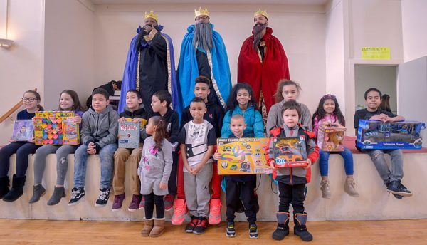 Men dressed as kings pose with children.