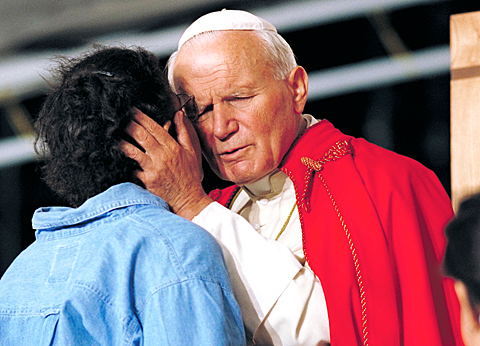 Pope John Paul II hugs a young woman during the closing Mass for World Youth Day in Denver in this Aug. 15, 1993, file photo. Italian newspapers were reporting that the pope was closer to being declared venerable following a Nov. 16 unanimous decision by the Congregation for Saints' Causes. (CNS photo/Joe Rimkus Jr.) (Nov. 17, 2009) See JPII-VENERABLE Nov. 17, 2009.
