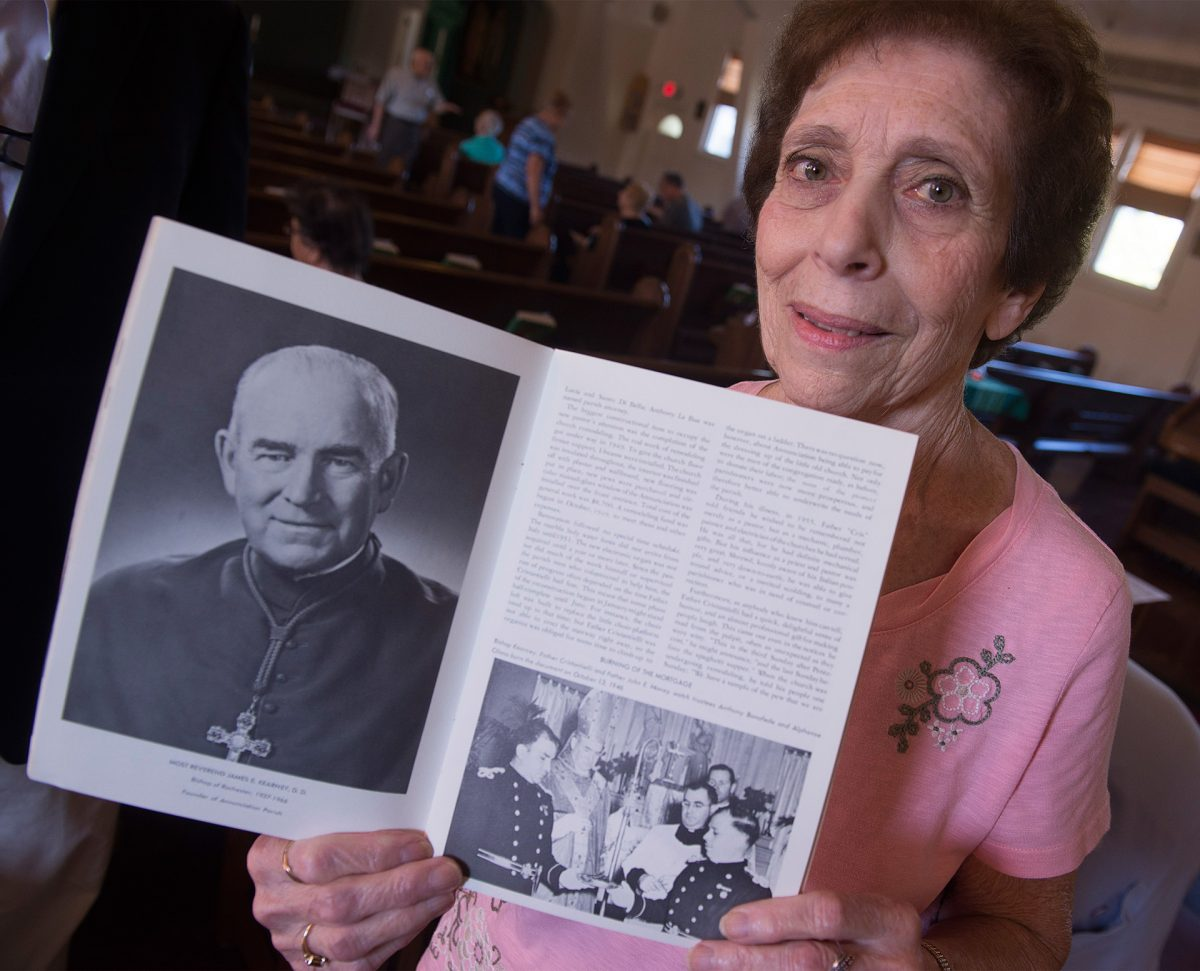 Lifelong parishioner Rose Giovine holds a book from the Golden Anniversary of Aunnunciation Church before the start of mass on Sept. 23 in Rochester. Pictured is Bishop James Kearney ,left, and Bishop Kearney, Father Cristantielli, Father John Money,, watch Anthony Bonafede and Alphonse Cilano (Giovine father) burn the mortgage in Oct. 13, 1946. Courier Photo by John Haeger