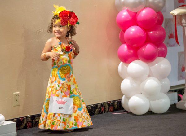 Girl smiles in dress.