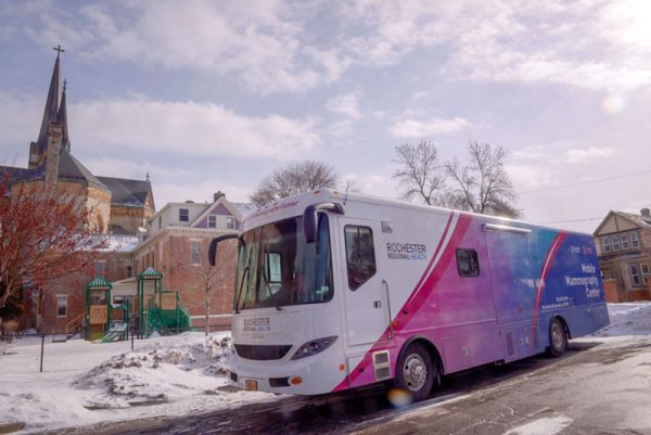 A health bus is parked outside of a church.