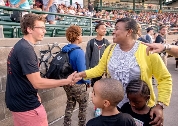 Woman shakes hands with kids.