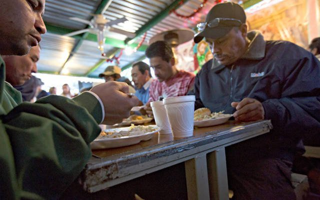 A group of men sit down to eat in the kitchen of the Aid Center for Deported Migrants in Nogales, Mexico, Dec. 20, 2015. The center is a project of the Kino Border Initiative, a binational church ministry for migrants. (CNS photo by Nancy Wiechec)