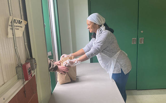 Deb Best hands out to-go meals at the door of Elmira Community Kitchen. Deb Best hands out to-go meals at the door of Elmira Community Kitchen.