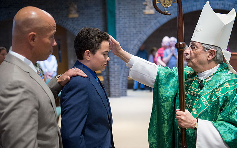 Bishop Salvatore Matano anoints head of Luke Medina with the oil of chrism as Confirmation sponsor  Colin Vega looks on during a mass at Church of the Resurrection in Fairport on August 4. Medina was unable to attend his confirmation in the spring with his class due to an open heart transplant. (Courier Photo by John Haeger)