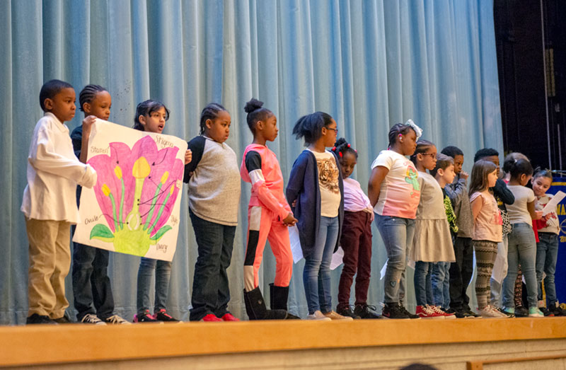 Students at Dr. Walter Cooper Academy School 10 present the anatomy of a flower during a school assembly April 5.