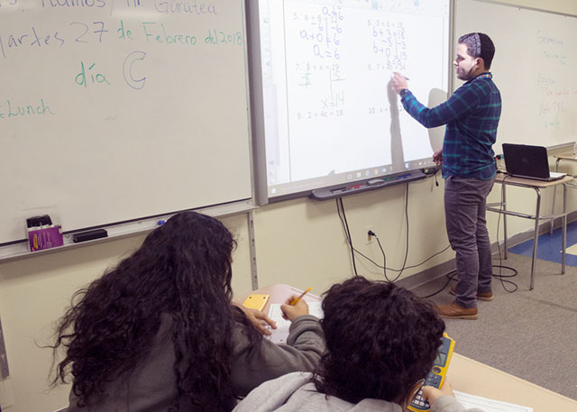 Jonathan Cruz-Colon goes over a math  problem on a white board with 7-8 grade student on Feb. 27 at the Bilingual Academy. The school was set up to meet the need of recent students coming from Puerto Rico. Courier Photo by John Haeger