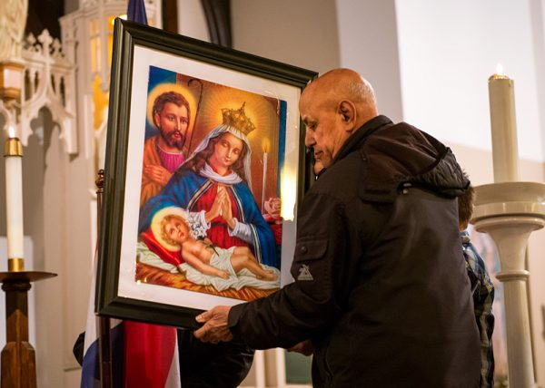 Cecilio Muñoz places the image of Our Lady of Altagracia on display at the start of Mass.