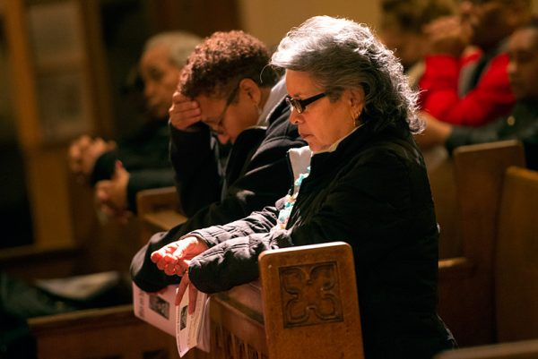Celine Rodriguez kneels in prayer during the Liturgy of the Eucharist.