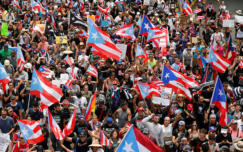 People join a rally to celebrate the resignation of Puerto Rican Gov. Ricardo Rossello in San Juan July 25, 2019. The Puerto Rican bishops said July 24 that in the wake of the historic  resignation island residents must continue to maintain their unity to overcome the social ills that led to the political and economic crisis. (CNS photo/Marco Bello, Reuters) See PUERTO-RICO-ROSSELLO-GONZALEZ July 25, 2019, and PUERTO-RICO-BISHOPS-RESIGNATION July 26, 2019