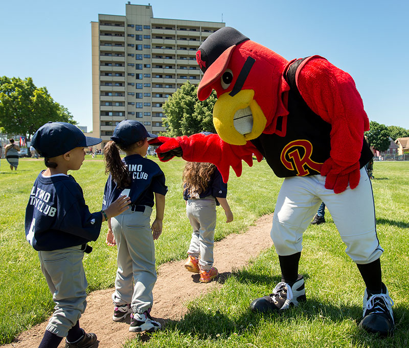 Spikes, the Rochester Red Wings mascot, greets players as they finish the parade.