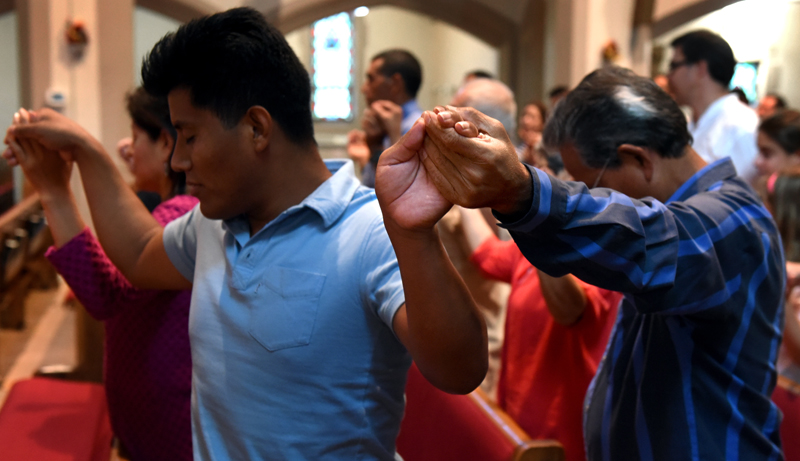Victorian Hernonde Morales, left, holds hands with Mario Escalante during the Our Father during the Bienvenida/Welcoming Celebration for the Brockport Migrant Farmworkers at the Church of the Nativity of the Blessed Virgin Mary Sunday Sep. 11.