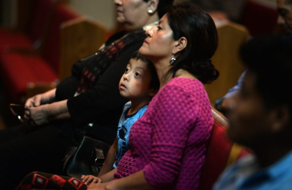 Axel Rodriguez, 4, listens with his mother, Libra Paz during the Bienvenida/Welcoming Celebration for the Brockport Migrant Farmworkers at the Church of the Nativity of the Blessed Virgin Mary Sunday Sep. 11.