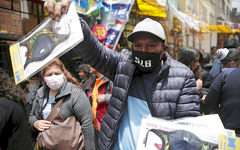 A man sells holds up face masks for sale on the street in La Paz, Bolivia.