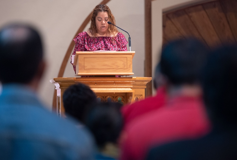 Woman reads prayers at church.