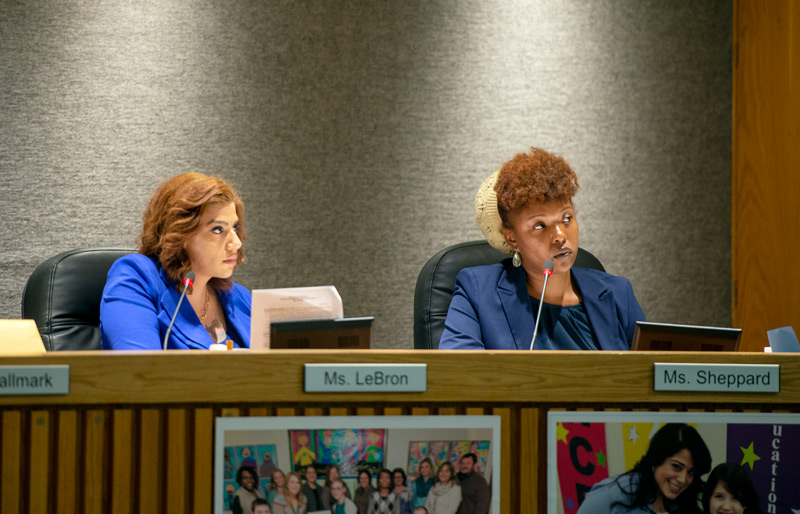 School board members Beatriz LeBrón (left) and Natalie Sheppard listen to the school budget presentation May 15. LeBrón and Sheppard each voted against the new budget.