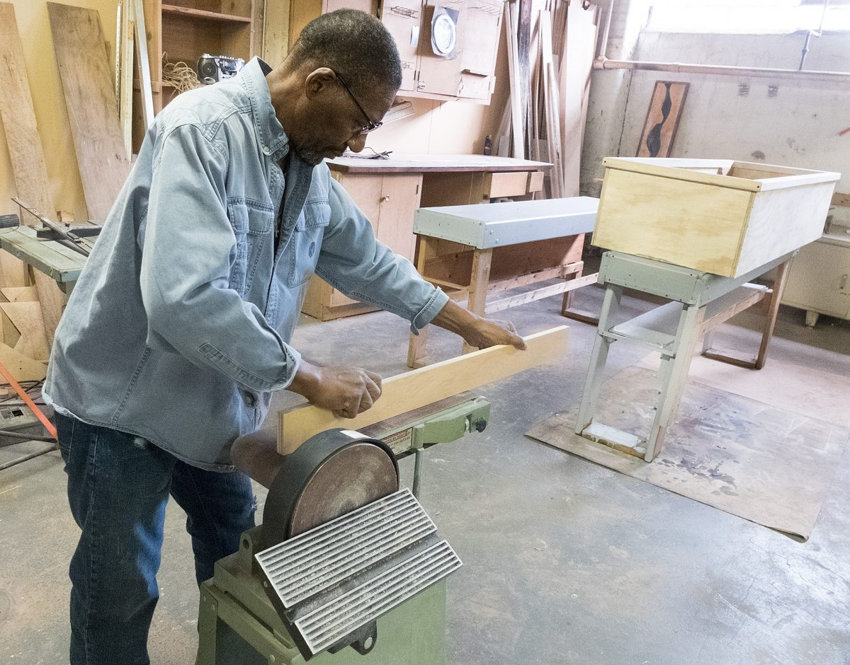 St. Joseph House of Hospitality volunteer Richmond Futch uses a beltsander to finish a wood board for  a casket at their workshop in Rochester on Oct. 24. Courier Photo by John Haeger.