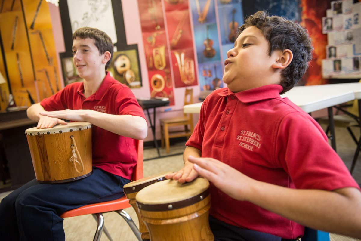 St. Francis-St. Stephen School fifth grader Evan Espinosa (right) along with classmate take part in a drum circle on Jan. 24 at the school. Courier photo by John Haeger