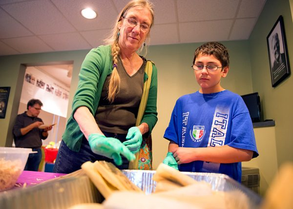 Sue Erdle and her grandson, Joey Yamonaco, place their tamales into a baking dish.