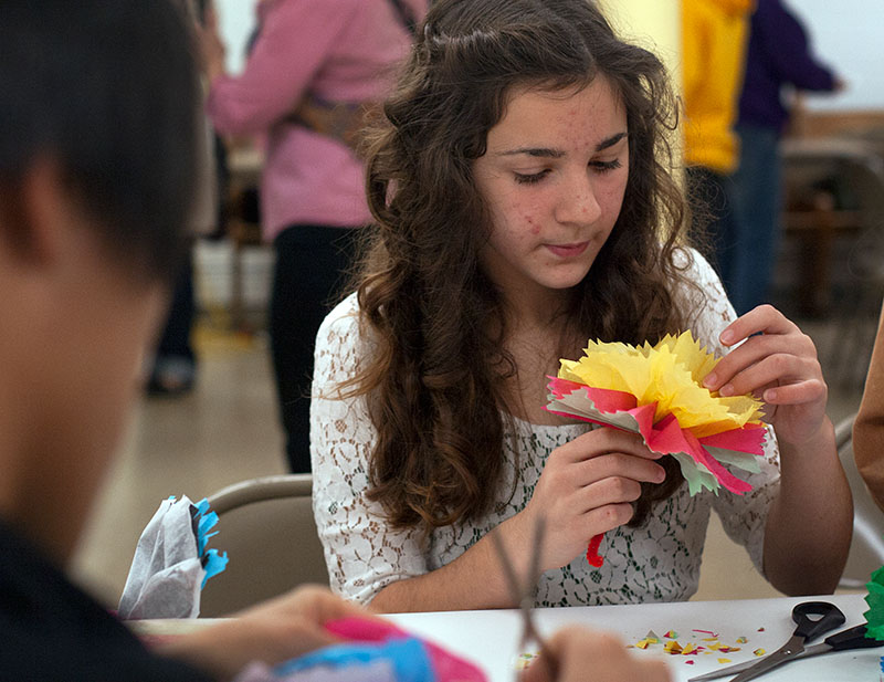 Katharina Nieves makes a flower out of tissue paper and a pipe cleaner during the Day of the Dead celebration.