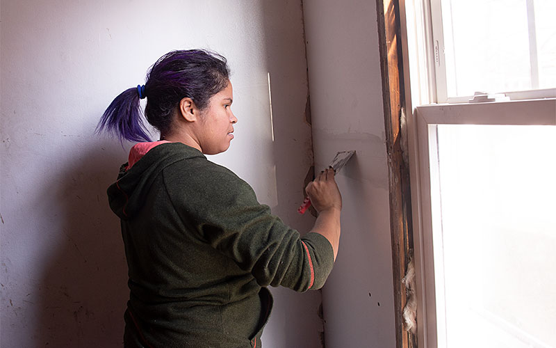 Ana H Martinez works to finish dry walling a section of the stairway  at 228 Melville Street in Rochester on Nov. 26.as part of the City Roots Community Land Trust of Rochester.(EMC photo by John Haeger)