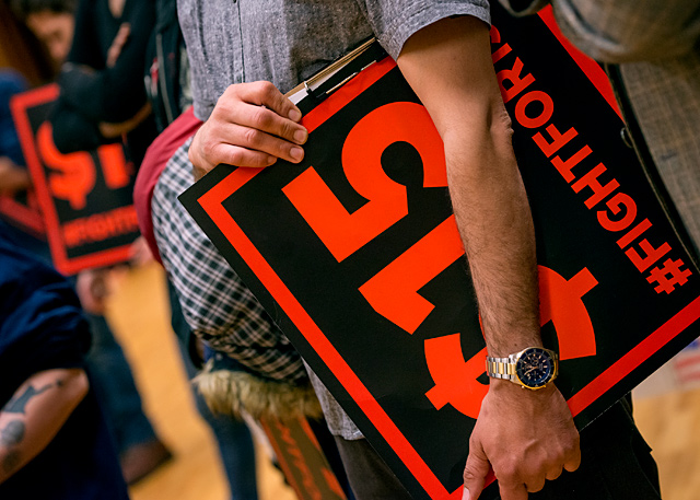 A rally attendee holds a Fight for 15 sign under his arm during a May 1 demonstration at the Lutheran Church of Reformation in Rochester.