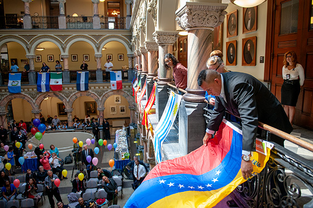 Rochester Police Department Officer Manny Ortiz unfurls the Venezuelan flag during an unfurling ceremony Sept. 15, 2014 in celebration of Hispanic Heritage Month. Officer Ortiz passed away unexpectedly Nov. 2.
